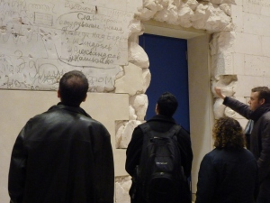 Maxwell students and alumni observe the graffiti left by Russian soldiers in 1945, preserved on a wall in the Reichstag in Berlin, Germany